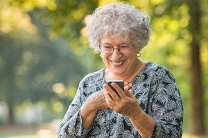 Cheerful old woman excited on receiving some good news over smar