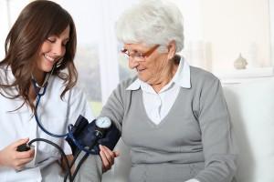 Closeup of nurse checking senior woman blood pressure