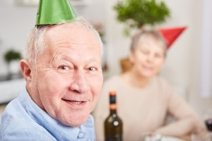 Senior in new year's eve celebration with party hats